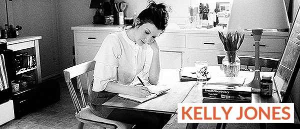 Kelly Jones writing a diary at a kitchen table near a stove a plant, french vocabulary book, chair and lamp.